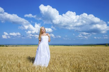 Young beautiful woman in a long white dress is standing in a whe
