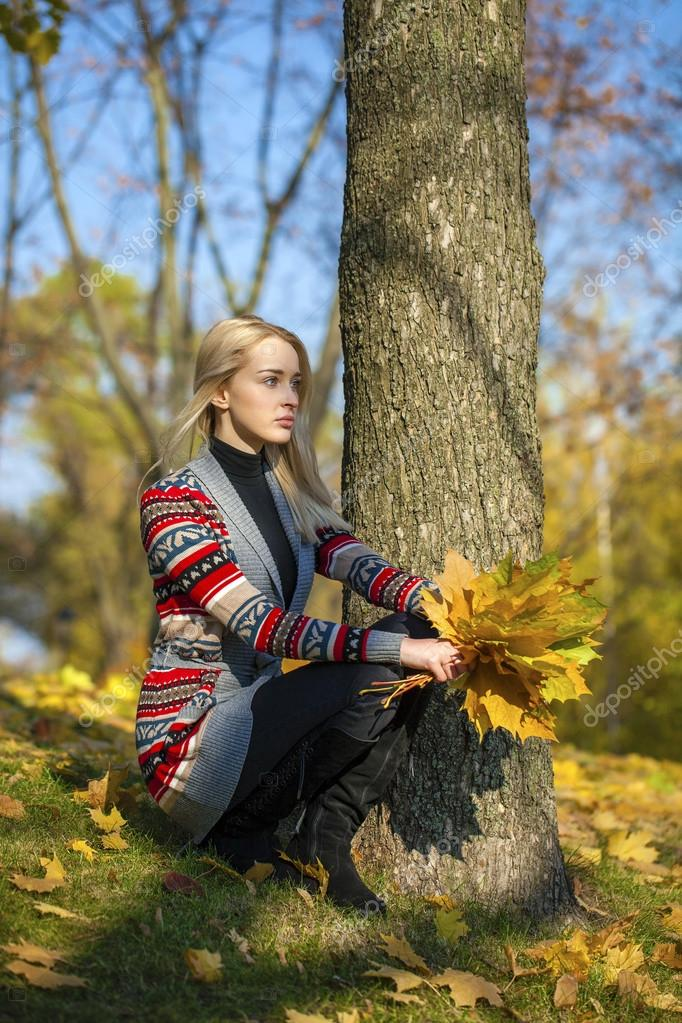 Happy Beautiful blonde woman walks in autumn park