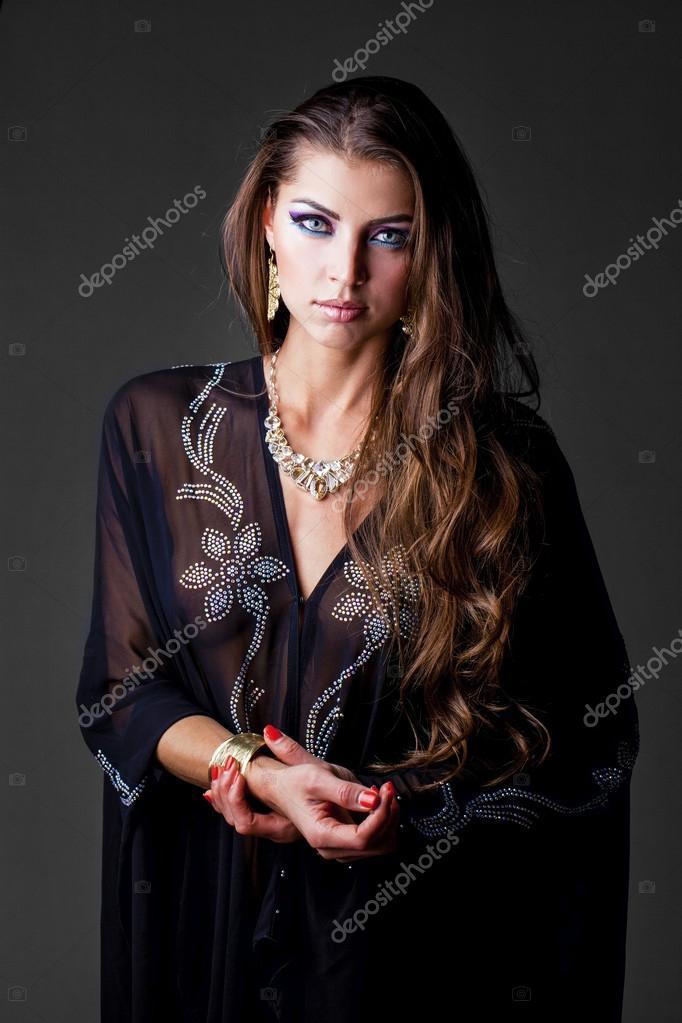 Stáhnout royalty-free Krásná mladá sexy žena v černé čarodějnice kostým a čepice, s koštětem a černá kočka ve svých rukou, při pohledu do kamery a usmívá.
