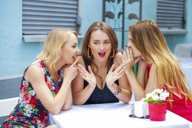 Three beautiful girlfriends gossiping woman sitting at a table i