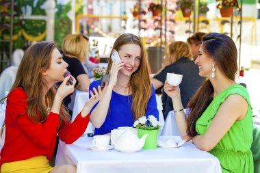 Three happy beautiful girls girlfriend drinking tea in a summer