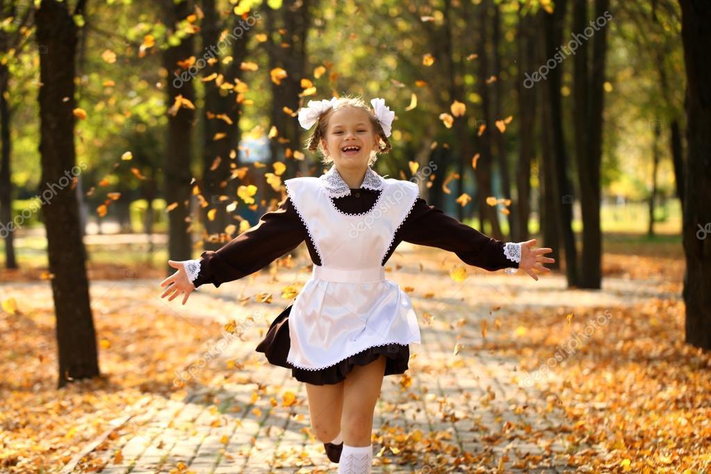 Happy little schoolgirl go home from school