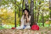 Boldog szép nő ül az őszi par telefon hívás
