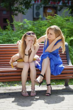Two young beautiful women secret at summer green park