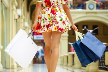 Legs of shopaholic wearing red dress while carrying several pape
