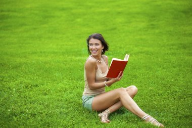 Young beautiful brunette girl reading a book outdoor