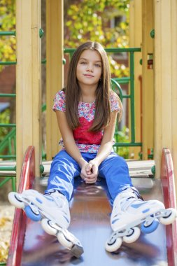 Portrait of little girl sits on a playground in roller skates