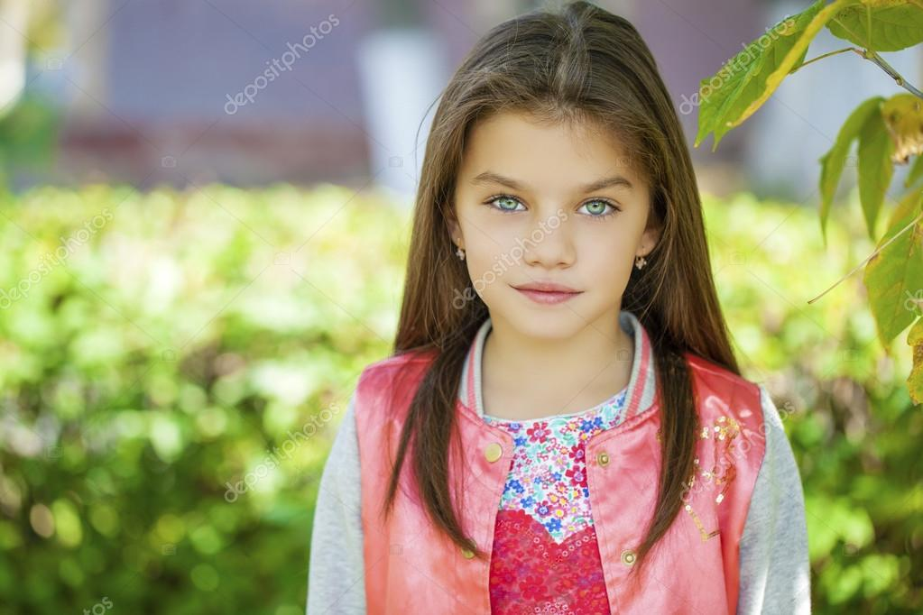 Beautiful little girl on green background of summer city park