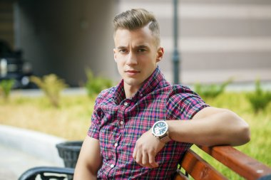 Calm handsome man in plaid shirt on the background of summer str