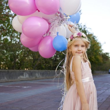 Little five-year girl in a pink dress holding balloons