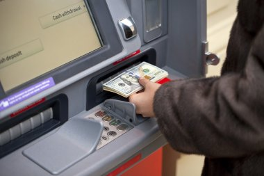 Woman hand showing dollar banknotes in front of the atm