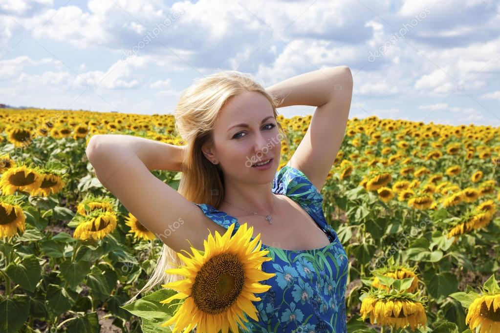 Portrait of a beautiful young blonde woman in blue dress on a ba