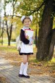 Photo Happy little schoolgirl in autumn park