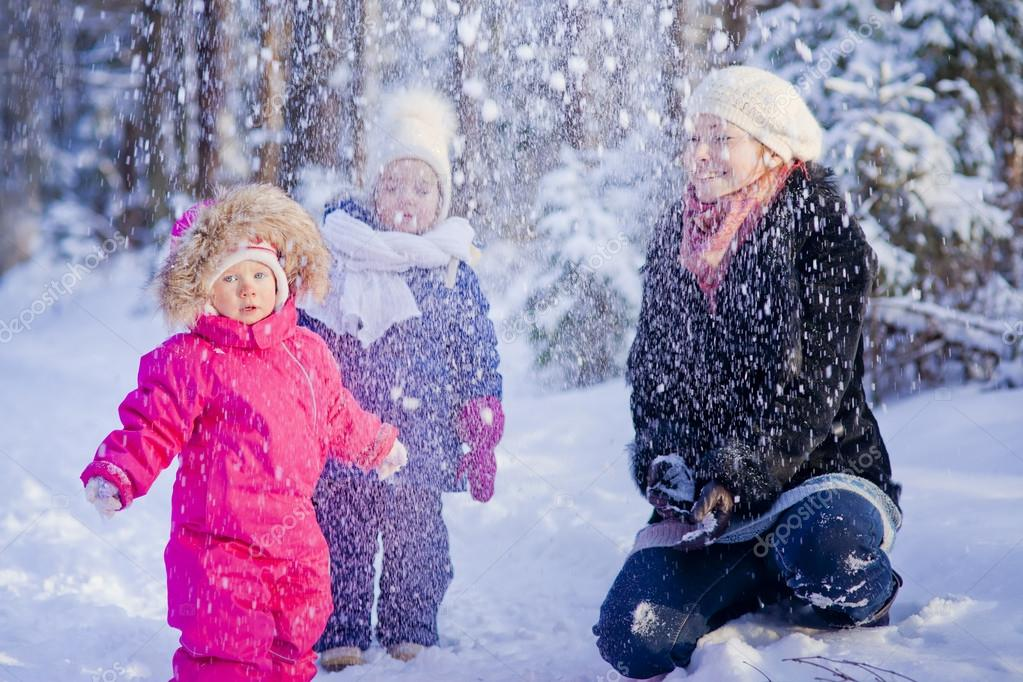 Mother and two children playing with snow