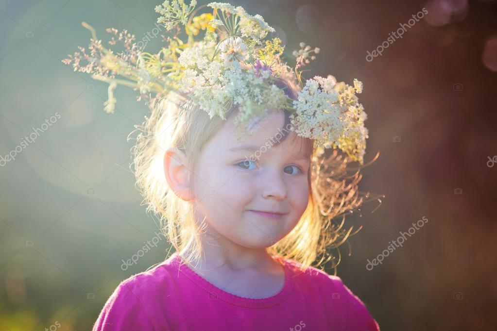 Cute little girl in flowers wreath