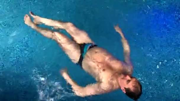 Tlustí muži plavou vzadu v bazénu.