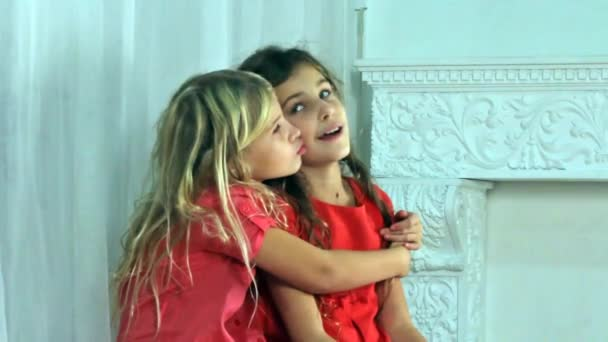 Young girl holding in her arms and kissing and having fun with her small sister.