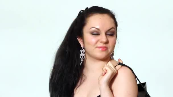 Modemädchen, schöne junge Frau posiert im Studio in schwarzem Kleid mit Tasche