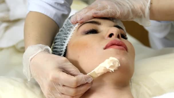 použití obličejové masky na obličej žena v salonu krásy