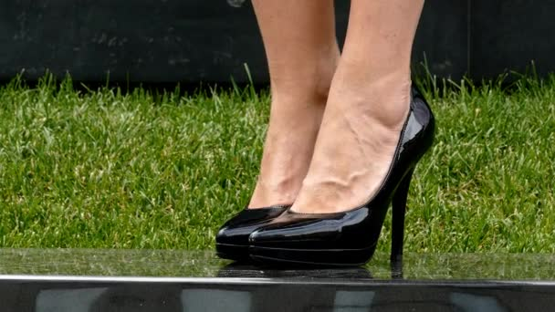 Close-up of young womans legs in high-heeled black shoes on marble plate in park