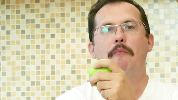 Dospělý člověk jíst zelené jablko s radostí