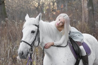 Two blonde, girl with a horse