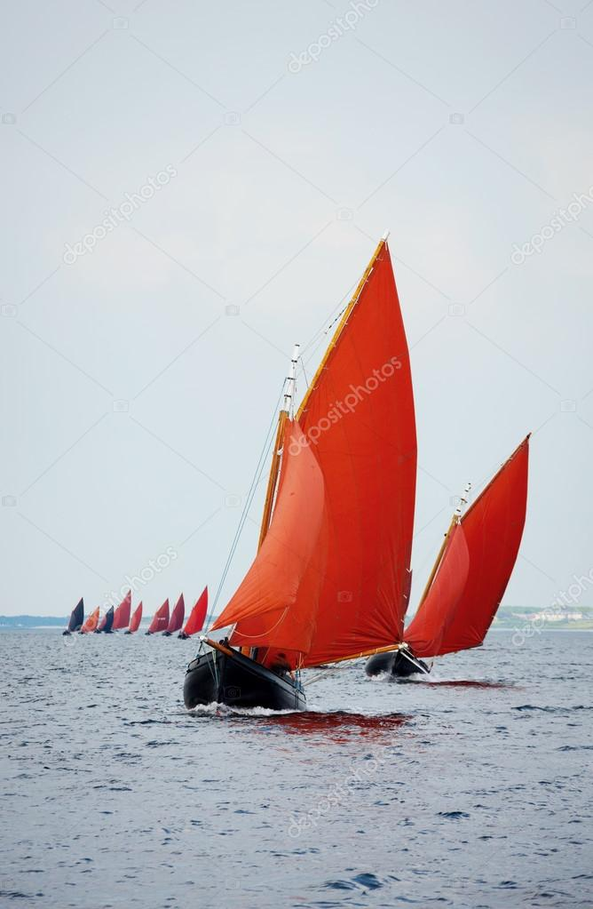 Traditional wooden boat with read sail.