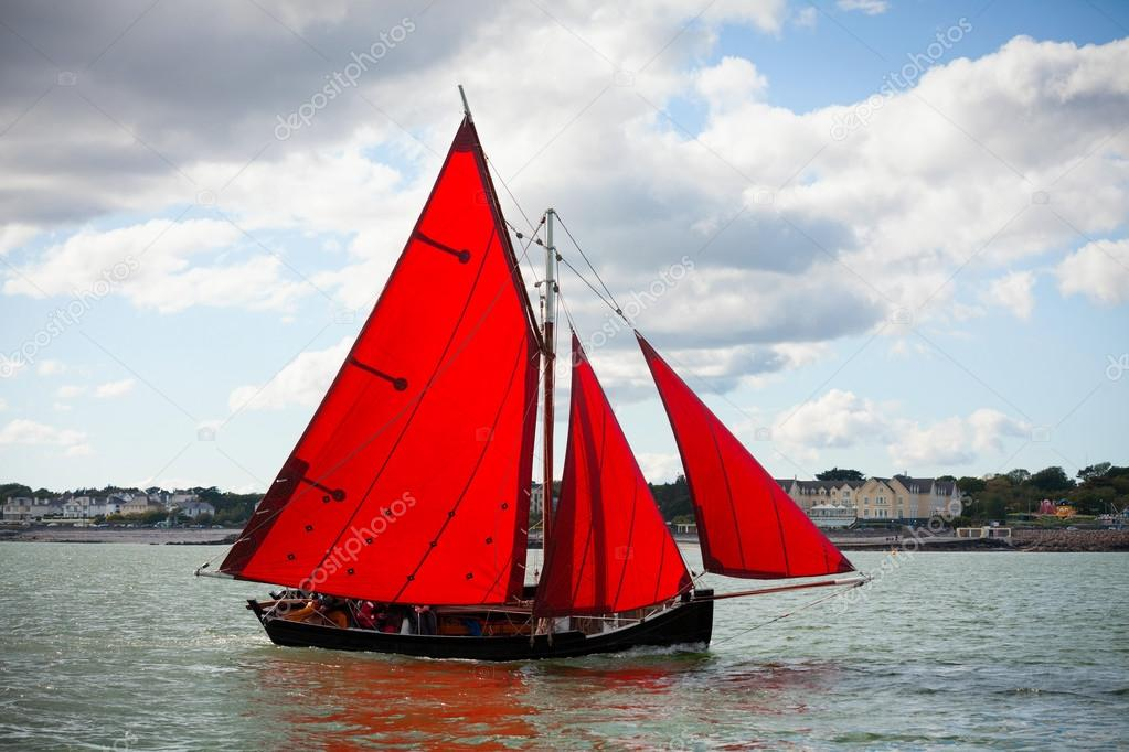Traditional wooden boats with red sail.