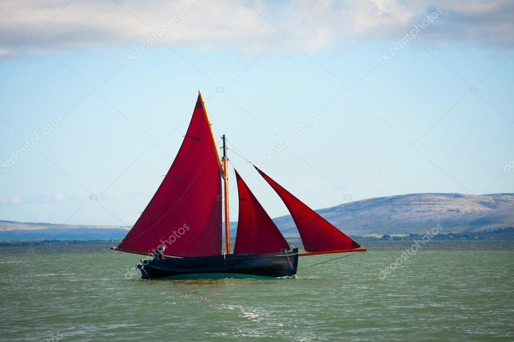 Traditional wooden boat with red sail.