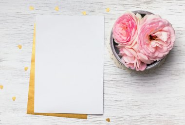 Blank paper and cute pink flowers on white wooden table