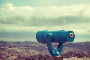Blue telescope and blurred city on background.