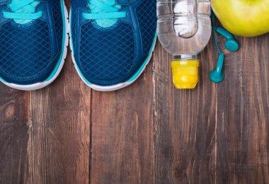 Sneakers, water, earphones  and apple on wooden background, top