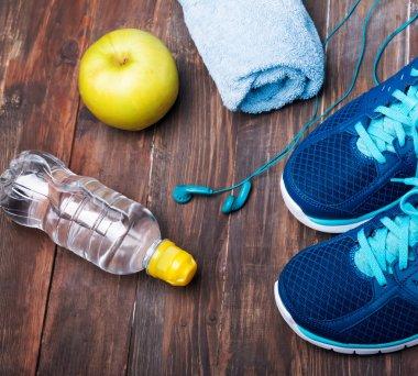 Sneakers, water, towel, earphones and apple on the wooden backgr