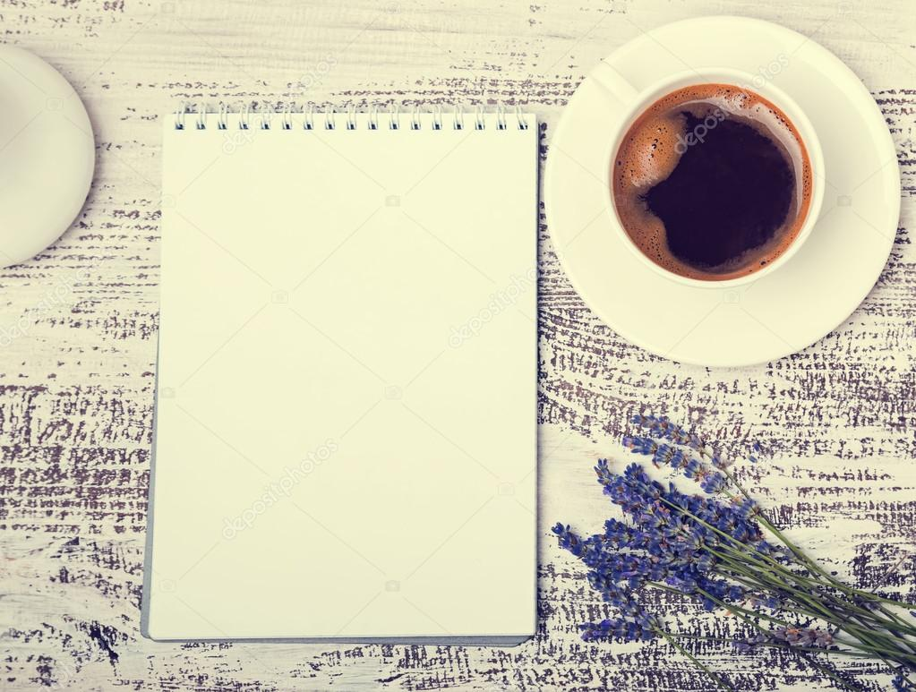 Empty notepad, cup of coffee and lavender flowers on white woode
