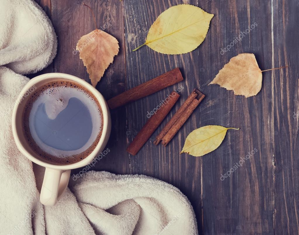Cup of coffee, books, blanket and yellow leaves