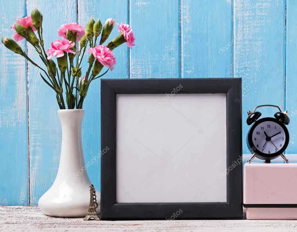Blank frame, pink flowers, alarm clock and souvenir Eiffel tower ...