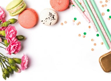 Macarons, paper straws, flowers and confetti on the white backgr