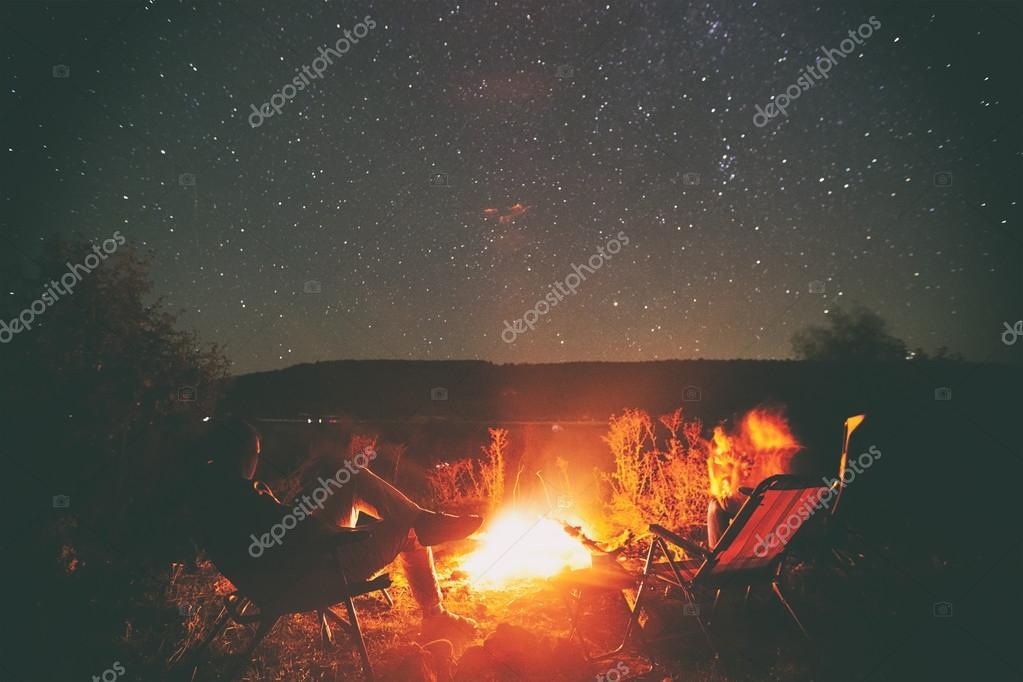 Friends sitting around campfire