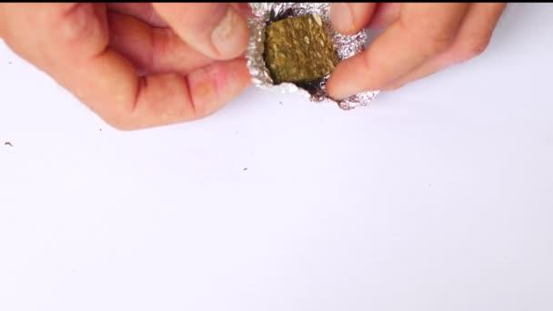 Mužské ruce vybalují lisovanou marihuanu