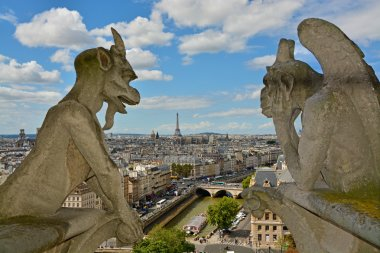 Notre Dame de Paris Cathedral. Famous Chimera (demon) overlooking the Eiffel Tower. Paris, France