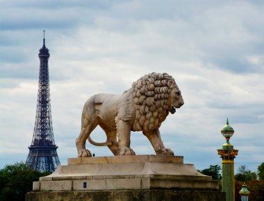 Statue of lion in Place de la Concorde against the backdrop of the Eiffel Tower, Paris, France