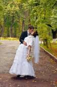 Fotografie Glückliches Hochzeitspaar. Braut und Bräutigam küssen im Park im Regen