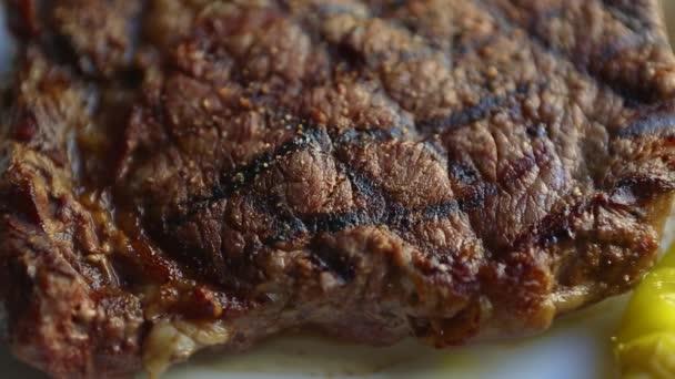 Grilovaný steak k večeři v restauraci. Lahodné hovězí maso vařené na grilu, podávané na bílém keramickém talíři, natočené shora s efektem oddálení. Gurmánský kousek červeného masa filet připravený k jídlu