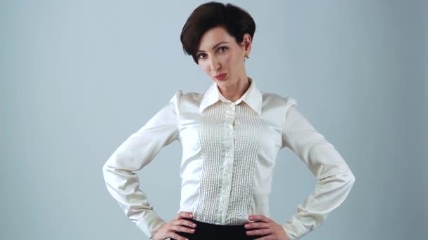 Gyönyörű fiatal üzletasszony pózol a stúdióban szürke háttérrel. Barátságos fehér nő visel klasszikus fehér selyem ing, piros rúzs üzleti találkozó