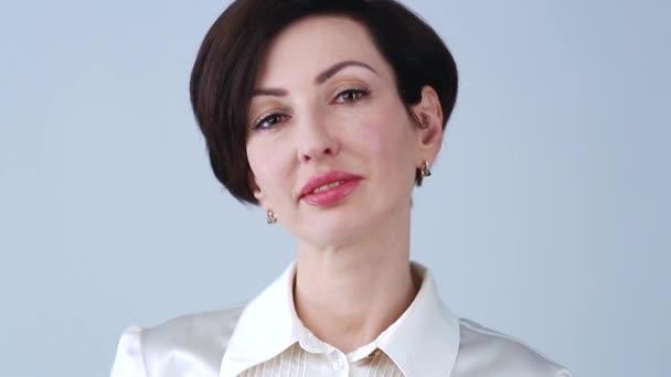 Videó portré gyönyörű fiatal üzletasszony pózol fehér formális ing piros rúzs és barátságos fogas mosoly. Gyönyörű fehér nő modell a 30-as években piros rúzst visel, formaruha