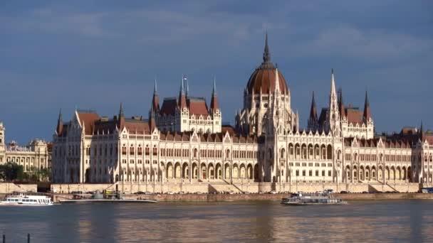 BUDAPEST, MAGYARORSZÁG - 2019. május 7.: Tavaszi évadban forgatják a Parlament épületét.A turisták sétahajója áthalad a Dunán Budapest történelmi központjában