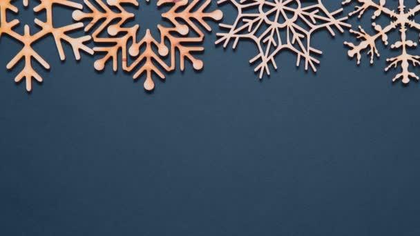 Pohybující se zimní prázdninové pozadí natočené v rovině leželo s prázdným prostorem pro text. Krásné ručně dělané dřevěné sněhové vločky na indigově modrém pozadí. Ručně kolébané figurky sněhové vločky z ekologického dřeva