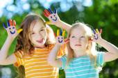 Adorable little sisters with painted hands