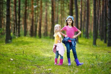 Adorable little sisters in forest