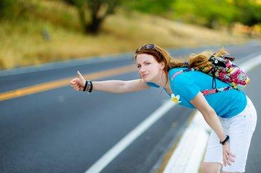 female tourist hitchhiking on road
